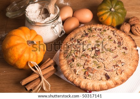 Pumpkin pie decorated with pecan nuts and walnuts - stock photo