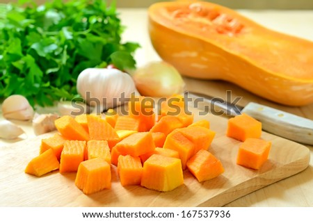 Pumpkin pieces on the cutting board on wooden table - stock photo