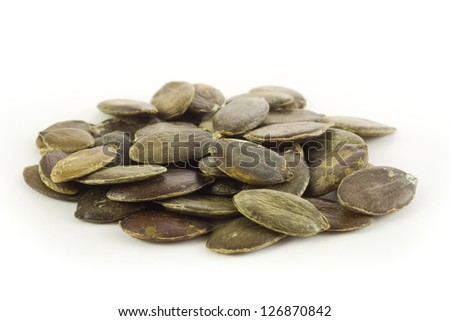 Pumpkin seeds on white background - stock photo