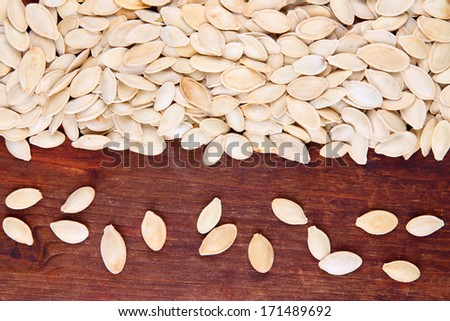 Pumpkin seeds on wooden background - stock photo