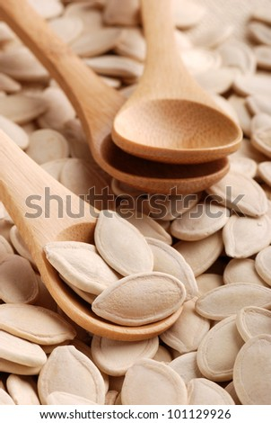 pumpkin seeds photographed up close with wooden spoons