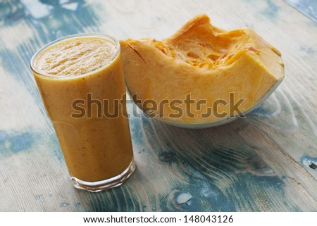 Pumpkin Smoothie. Healthy blended juice on rustic wooden table. Shot on daylight, shallow dept of field. - stock photo