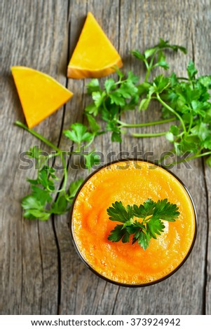 Pumpkin smoothie in glass on wooden background, top view - stock photo