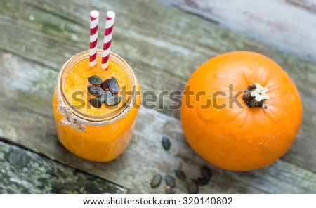 Pumpkin smoothie on rustic background - stock photo