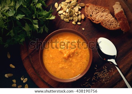 Pumpkin soup, bread and green on the wooden board. Delicious, vegetarian meal. Close-up with copy space. Toned image. - stock photo
