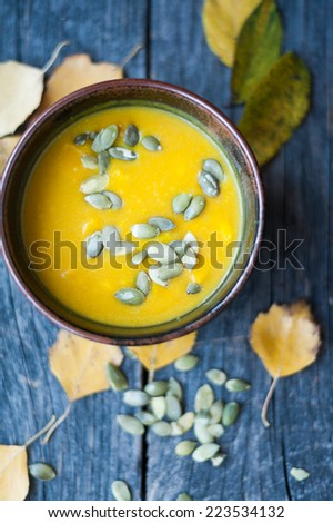 Pumpkin soup in a bowl on the table - stock photo