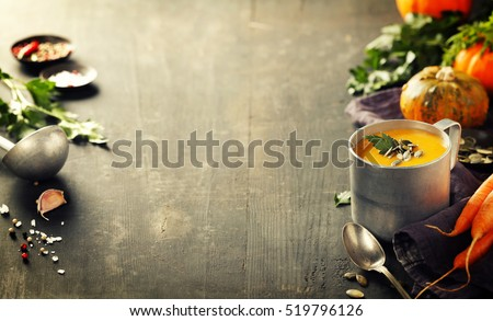 Pumpkin soup in a metal pot on a wooden surface