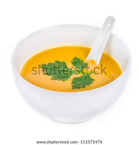 Pumpkin soup in a white bowl of white ceramic spoon and parsley isolated on white background