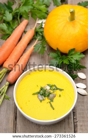 Pumpkin soup in bowl and fresh vegetables on rustic table - stock photo