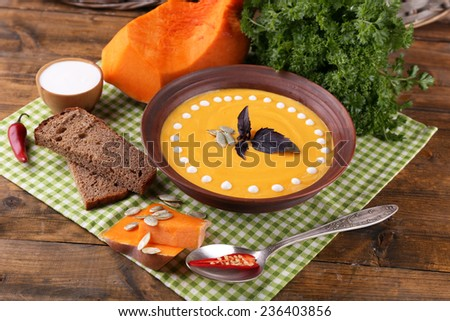 Pumpkin soup in color plate and pumpkin slice on napkin, on wooden background - stock photo
