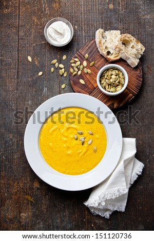 Pumpkin soup in white plate on wooden background - stock photo