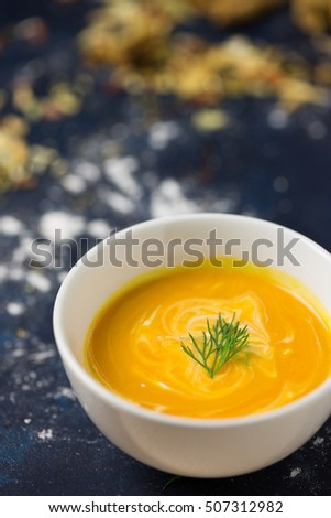 Pumpkin soup macro shot. White porcelain bowl. Piece of dill. Vegetables at the background. Selective focus.