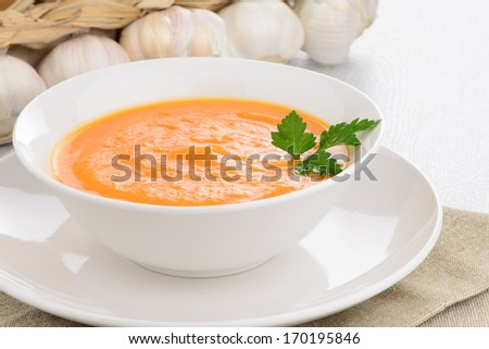 Pumpkin soup on white wood background. - stock photo