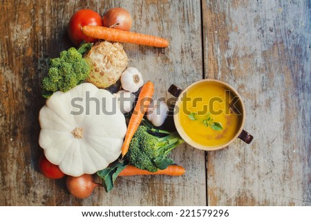 Pumpkin soup on wooden table - stock photo