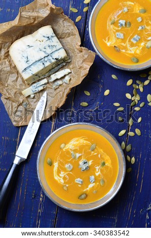 Pumpkin Soup with blue cheese and pumpkin seeds, vertical, selective focus - stock photo