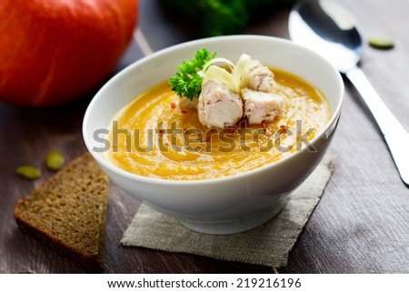 Pumpkin soup with chicken garnished with parsley leaf in white bowl on brown wooden table with slice of rye bread - stock photo