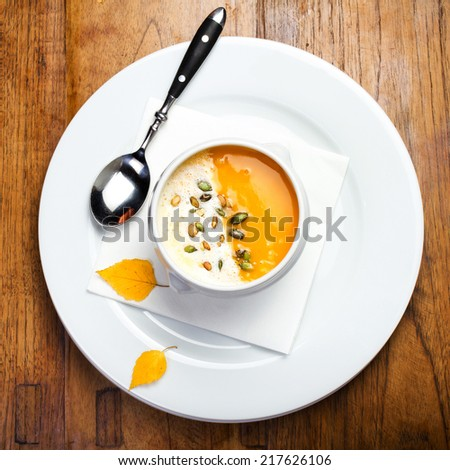 Pumpkin soup with cream and pumpkin seeds in a white bowl on wooden table - stock photo
