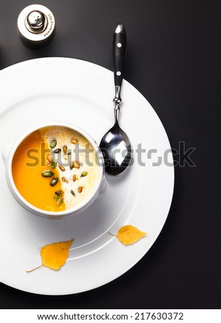Pumpkin soup with cream and pumpkin seeds in a white bowl over black background - stock photo