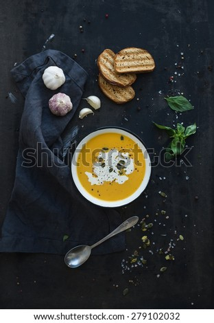 Pumpkin soup with cream, seeds, bread and fresh basil in rustic metal plate on grunge black background. Top view - stock photo