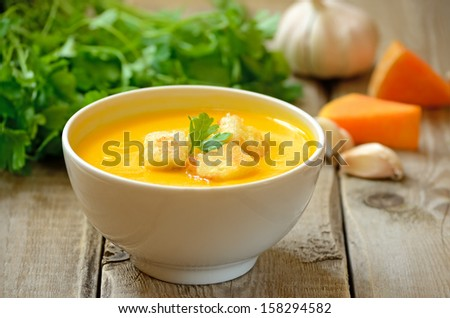 Pumpkin soup with croutons on wooden table - stock photo
