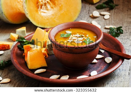 Pumpkin soup with oil and seeds in a clay bowl in a rustic style, selective focus