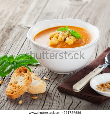 Pumpkin soup with pumpkin Seeds, cream and basil on rustic wooden background, selective focus
