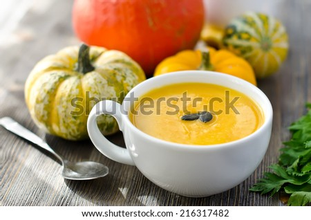 Pumpkin soup with pumpkins on wooden background  - stock photo