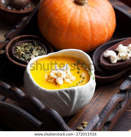 Pumpkin soup with salty popcorn in a white ceramic bowl with fresh pumpkin on a wooden background - stock photo