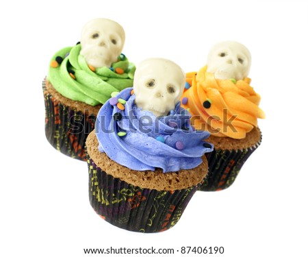 Pumpkin spice cupcakes decorated with skulls made of white chocolate - stock photo