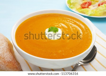 Pumpkin, sweet potato and carrot soup with a dollop of yoghurt, in a white bowl on a blue background, with salad and copy space. - stock photo
