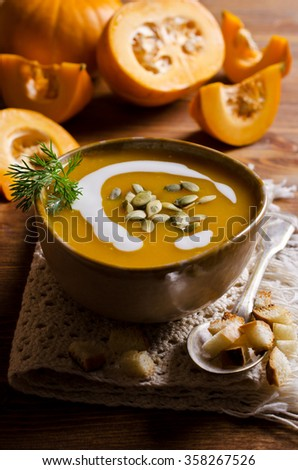 Pumpkin thick soup in rustic style on a wooden background. Selective focus.