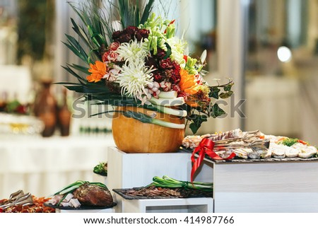Pumpkin vase with flowers as a part of dinner table decoration - stock photo