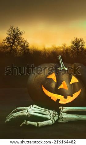 Pumpkin with skeleton hand with dark background - stock photo