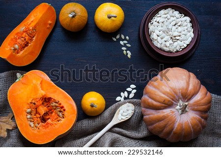 Pumpkins and a bowl with toasted pumpkin seeds, wooden spoon, leaves
