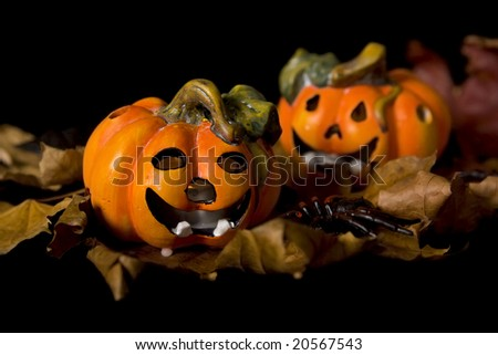 Pumpkins, autumnal leaves ad ghosts on a black