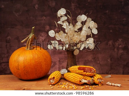 Pumpkins, corn and flowers on the table - stock photo