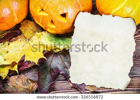 pumpkins for Halloween and sheet of paper on wooden background - stock photo