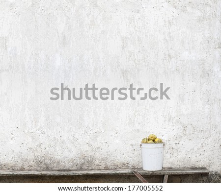 pumpkins in the bucket near the wall - stock photo