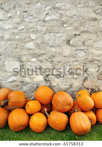 Pumpkins piled against a rustic stone wall - stock photo