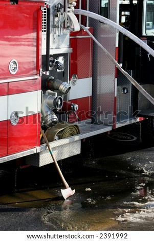 Pumps and axe at the side of a firetruck - stock photo
