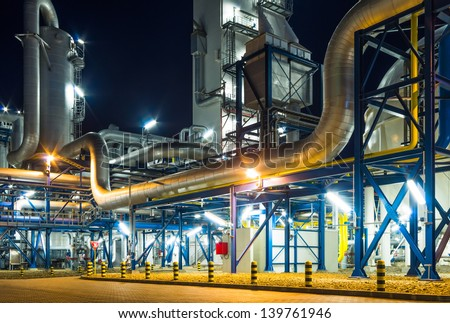 pumps and piping system inside of industrial plant at night - stock photo