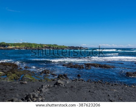 Punaluu Beach has black sand made of basalt and created by lava flowing into the ocean which explodes as it reaches the ocean and cools. - stock photo
