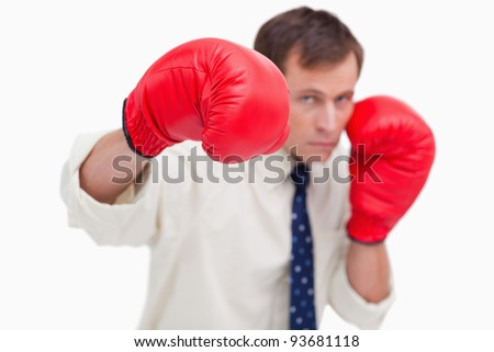Punching businessman with boxing gloves against a white background