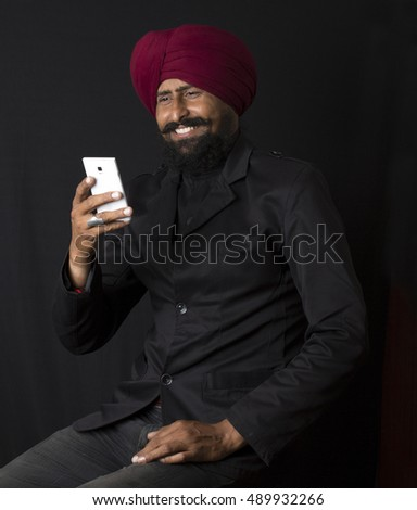 Punjabi young man also know as Sikh, Sikhism, Punjabi people or sardar talking with other people on mobile phone on black background