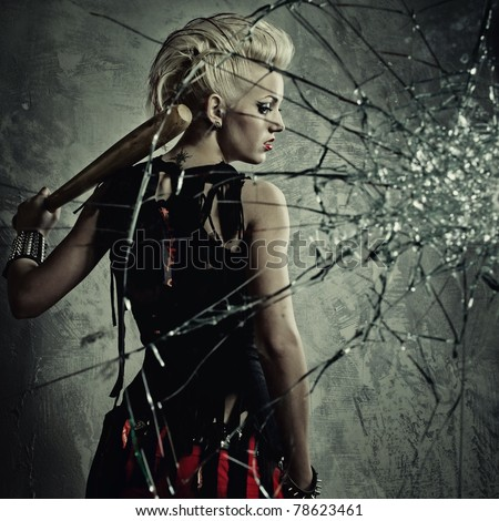 Punk girl with a bat behind broken glass - stock photo