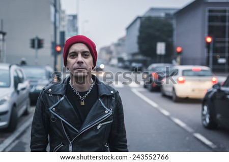 Punk guy with beanie posing in the city streets - stock photo