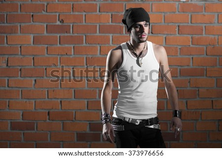 punk rocker stylish man in the white T-shirt and black jeans with red urban brick wall background