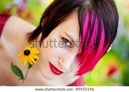 Punk woman with flower in the garden - stock photo