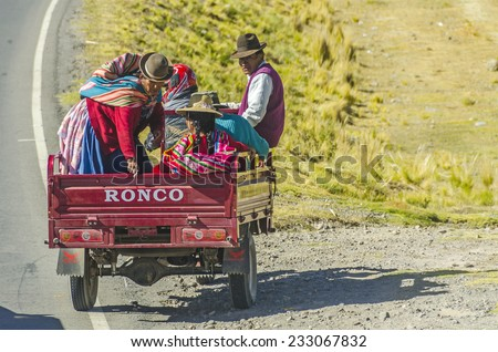 PUNO, PERU, MAY 6, 2014: Peruvian countryside in region of Lake Titicaca - Local people travel on motorcycle trailer - stock photo