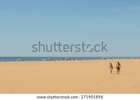 PUNTA DEL MORAL, SPAIN - MAY 2 2015. Tourists and locals enjoy the beautiful early May weather on Ayamonte's beach area on the Costa de Luz. The area has miles of golden sandy beaches. - stock photo